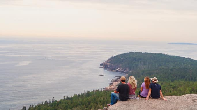 four friends overlooking the ocean in Acadia National Park