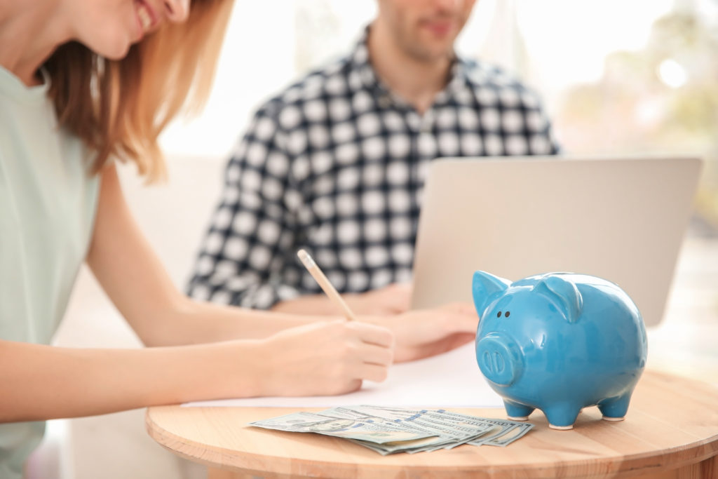 Piggy bank, money and blurred couple on background