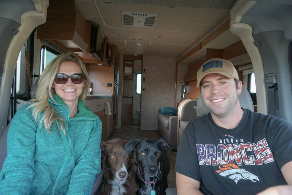 Young couple driving a motorhome with 2 dogs between them