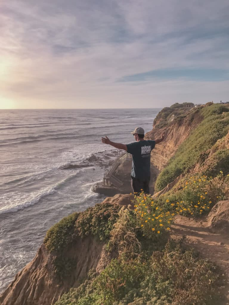 Man on edge of cliff overlooking the ocean with arms up
