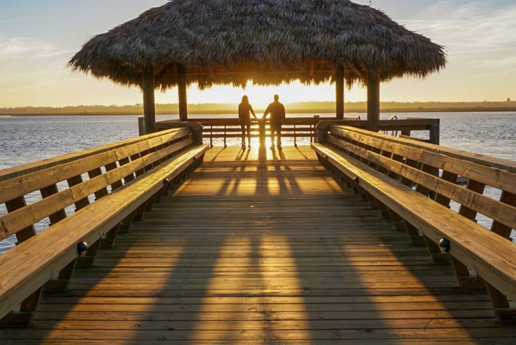 Couple standing at the end of a pier watching the sunset and holding hands in St. Augustine Florida