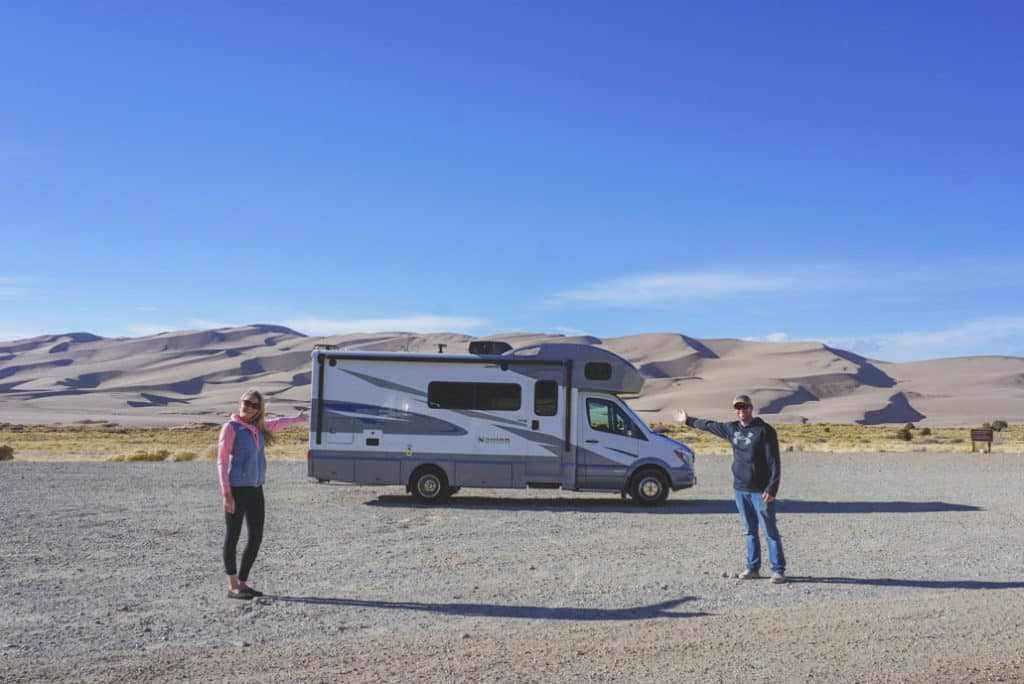 Young couple standing in front of RV at great sand dunes national park