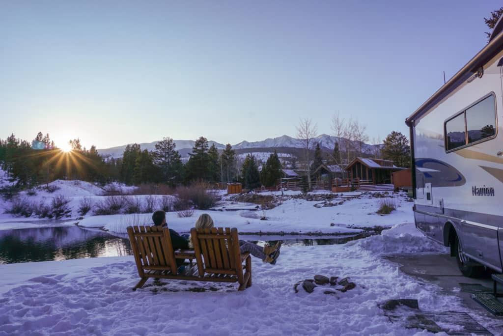 couple sitting by a pond in the snow by their RV