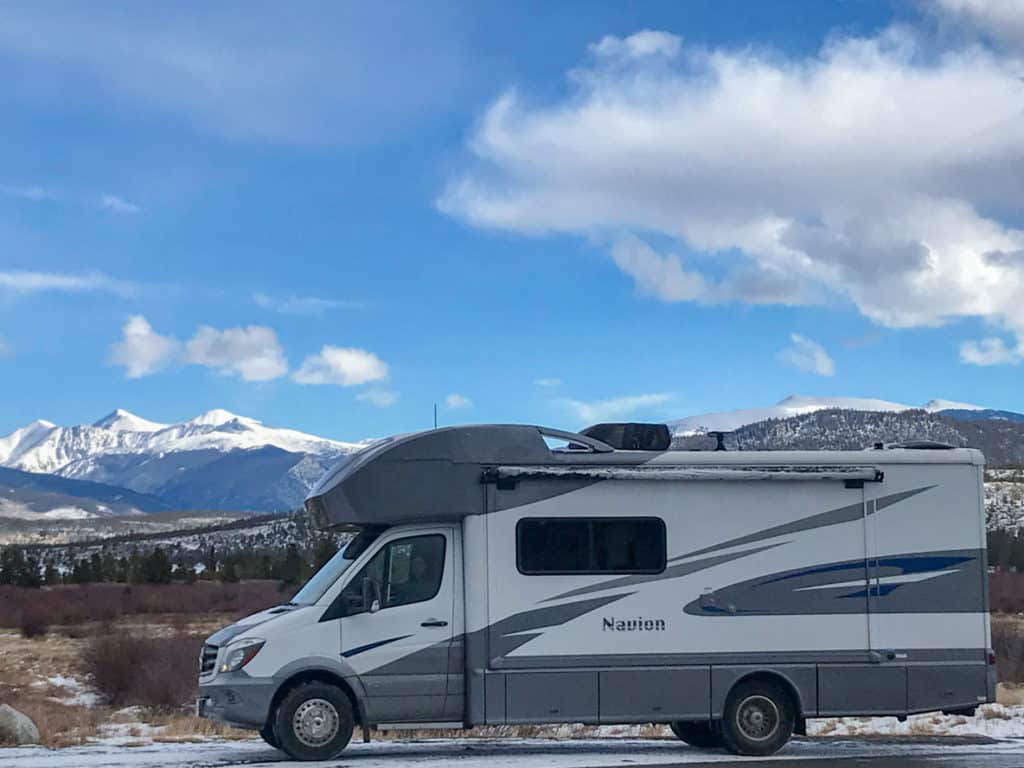 RV parked in front of snow capped mountains in Colorado in the winter