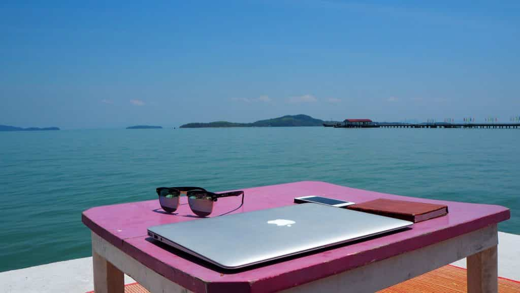laptop computer and sunglasses and cell phone overlooking the ocean in Thailand