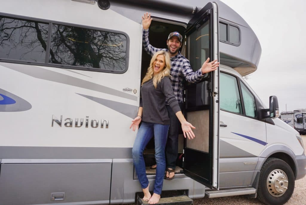 Young couple standing in RV excited