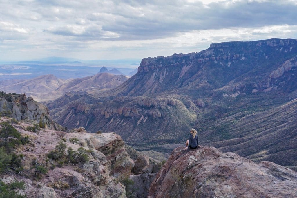Woman sitting on the edge of a cliff overlooking stunning mountain views in Big Bend National park Texas
