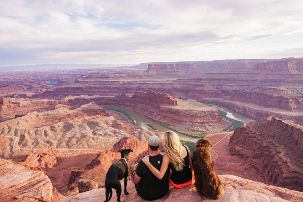 man and woman with two dogs sitting on cliff overlooking view at deadhorse point state park utah