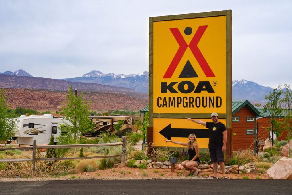 KOA sign with couple pointing to campground