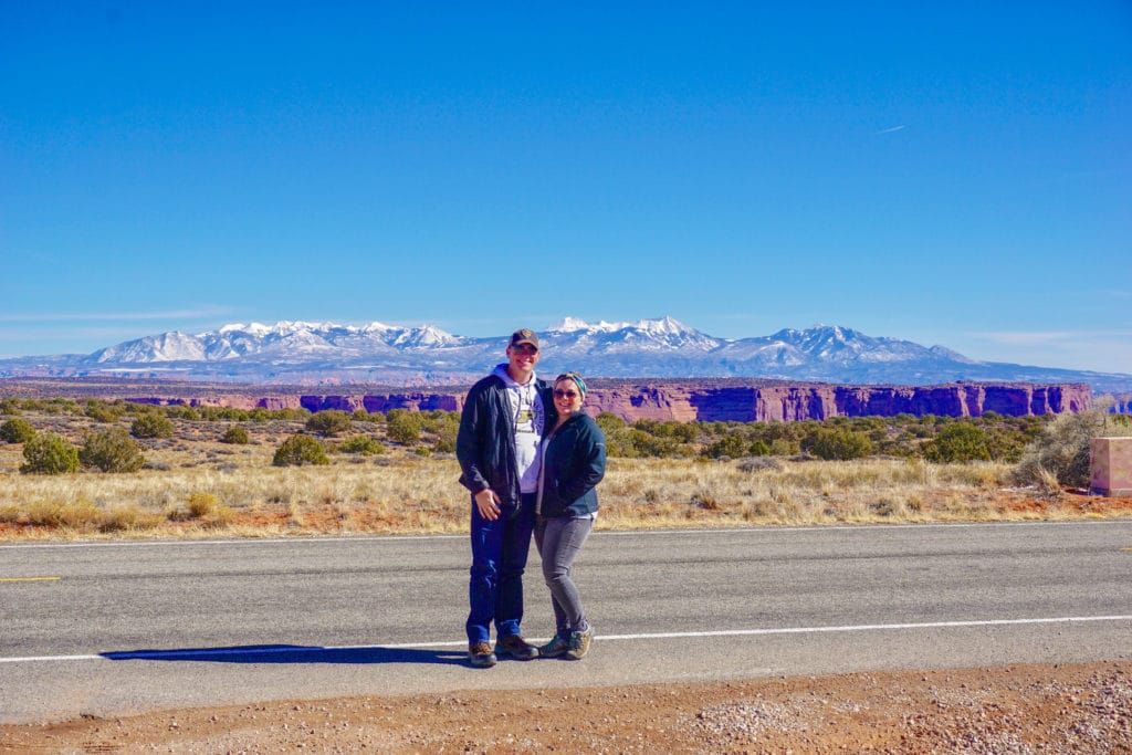 couple standing in road with scenic mountain view