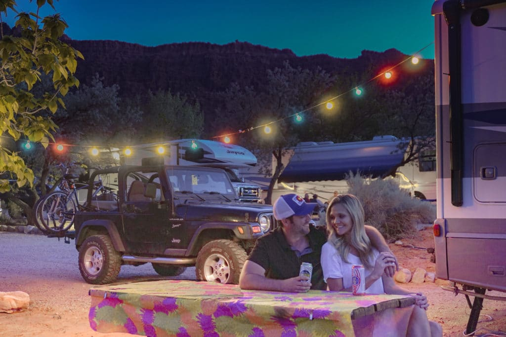 couple camping with string lights