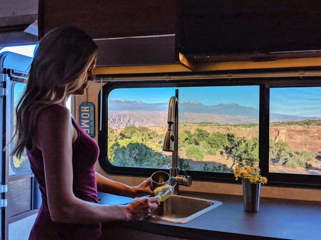 Woman doing dishes in an RV with beautiful view of Moab Utah in kitchen window