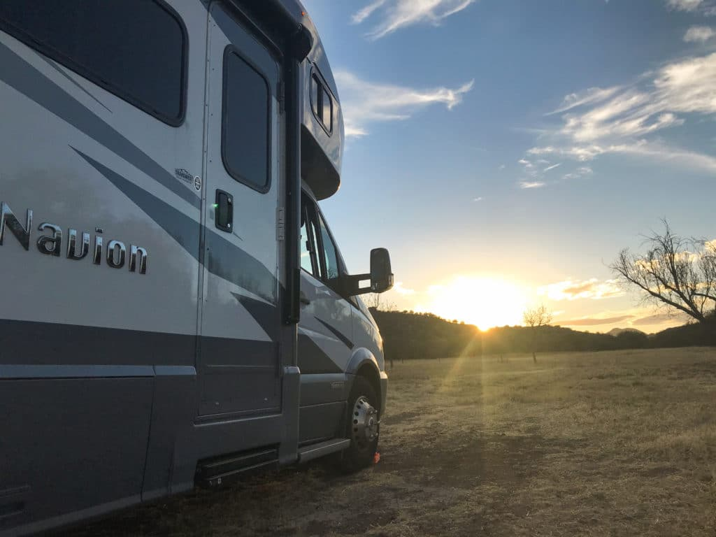 RV motorhome in open space with sun setting