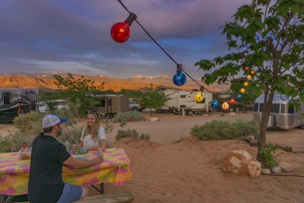couple camping eating at picnic table with string lights