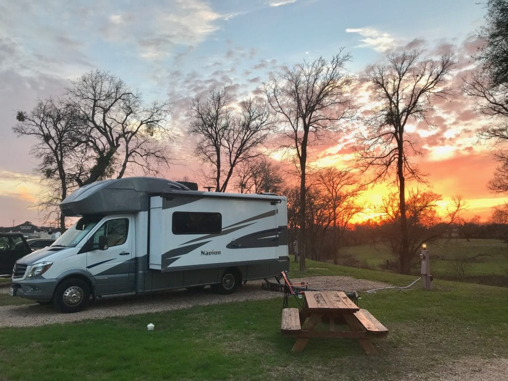 rv motorhome camped at an RV park with a beautiful sunset