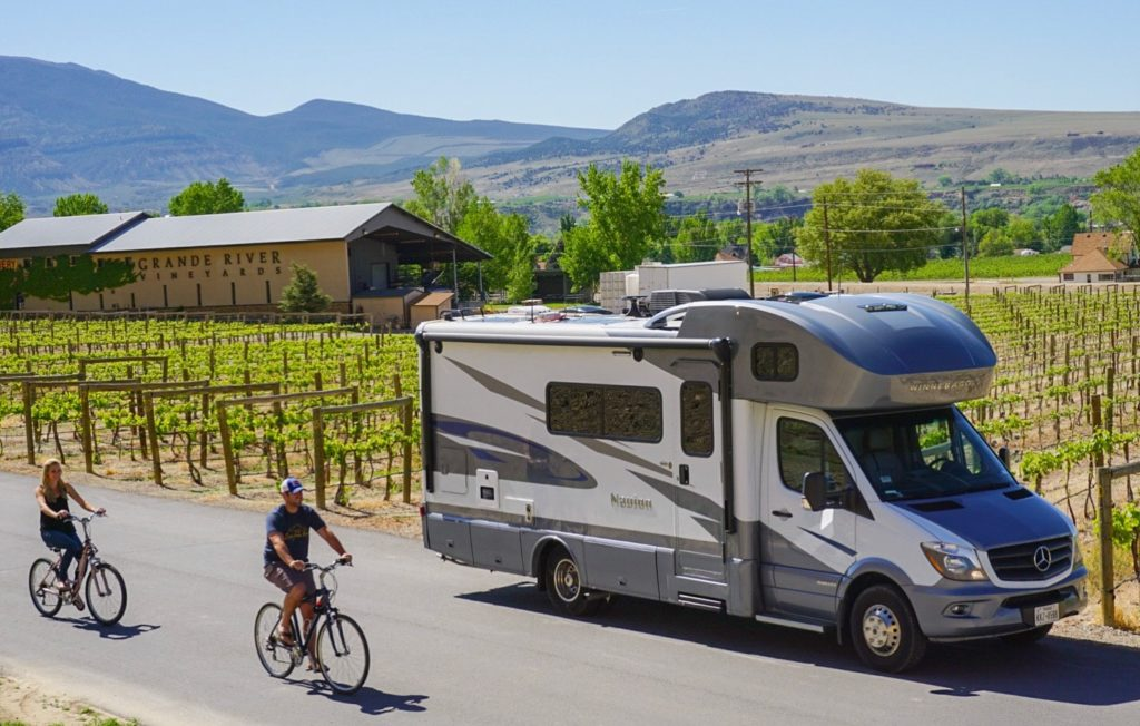 couple biking past RV motorhome parked at vineyard