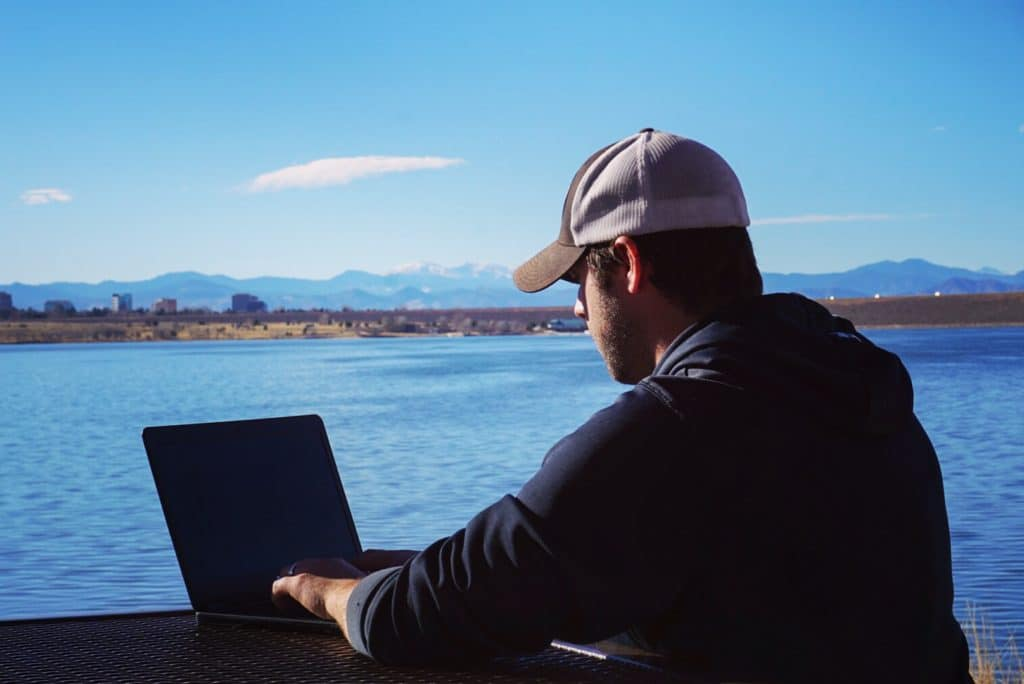 Man working on laptop by a lake