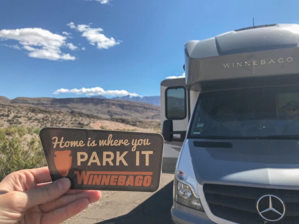 RV motorhome with sticker that says home is where you park it