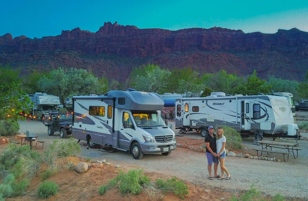 Couple standing by RV in campground in Moab Utah