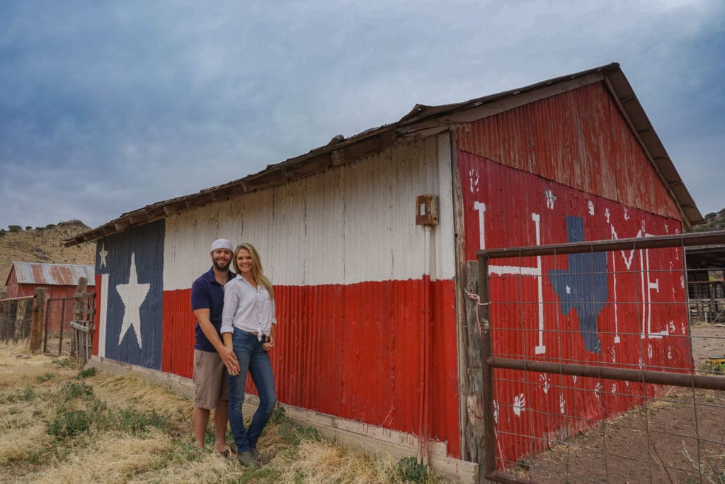couple standing in front of texas flag painted barn