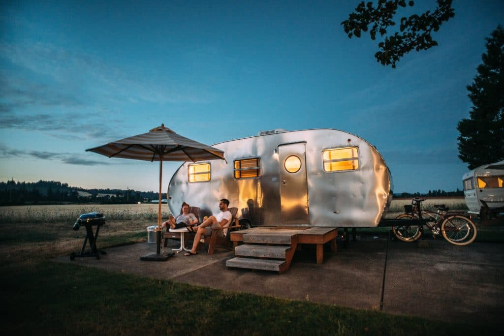 camper set up at night man sitting outside