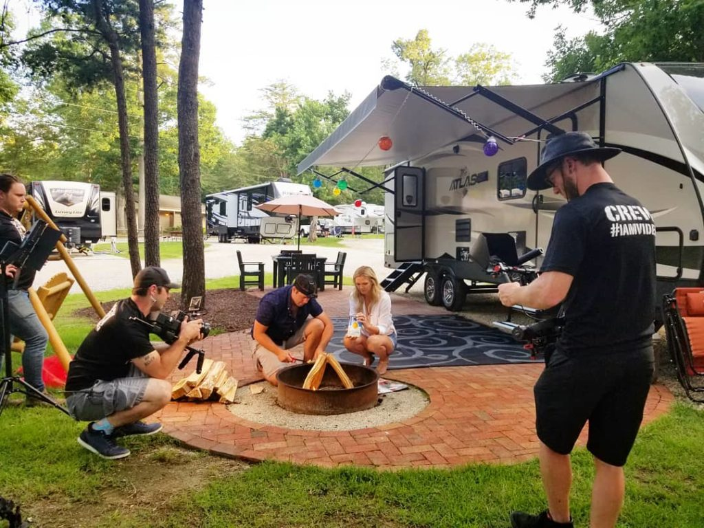 video crew filming a couple camping by an RV