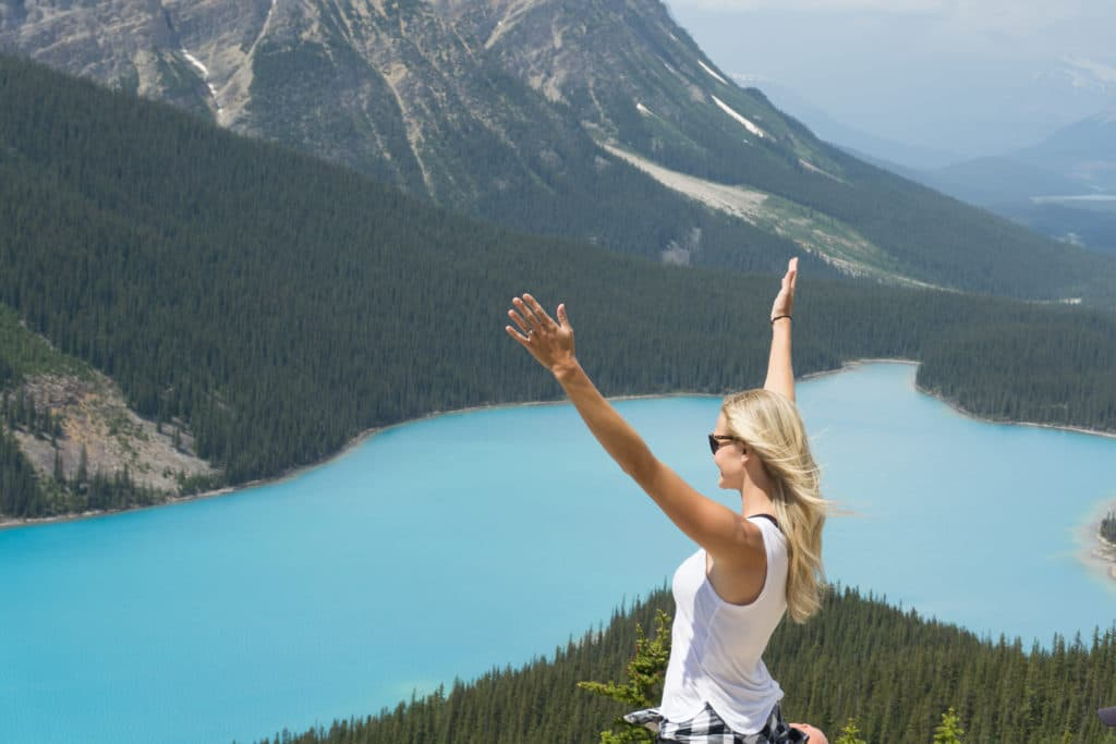 woman with arms raised at peyto lake in canada