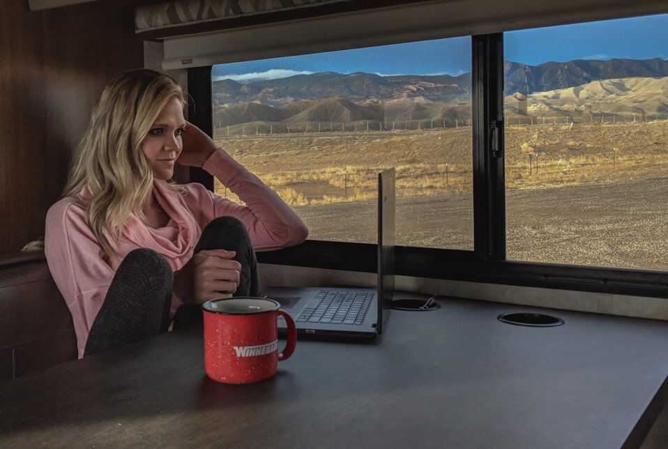 woman working on laptop in RV with mountain views outside window