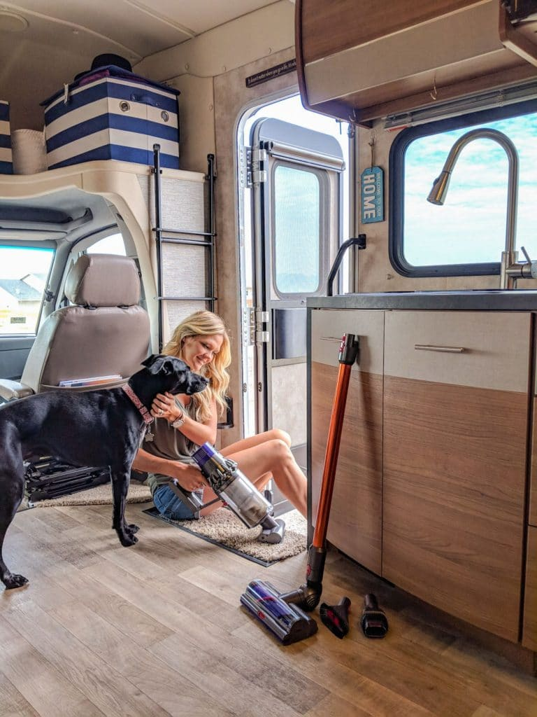 Woman vacuuming RV with Dyson vaccum and dog over her shoulder