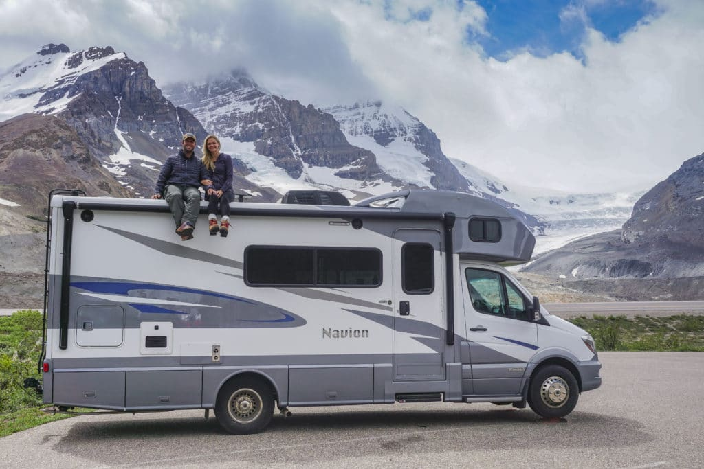 couple sitting on the roof of RV in front of glacier in jasper national park canada