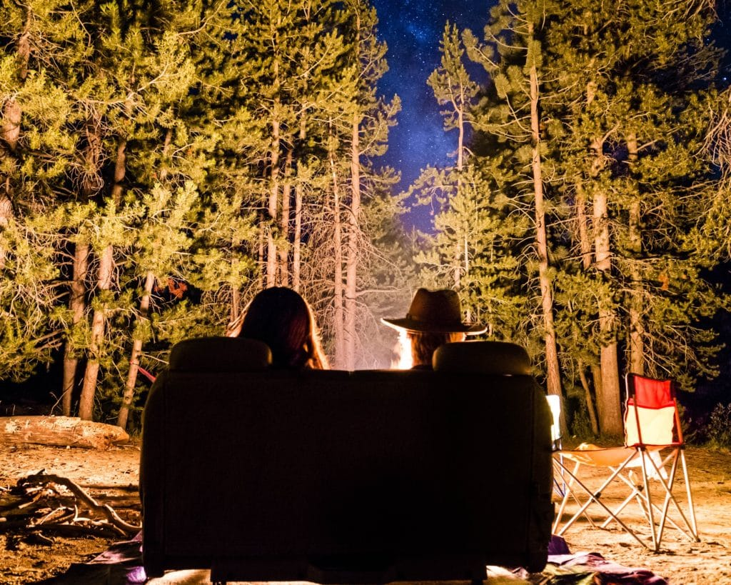Couple sitting together at a campfire