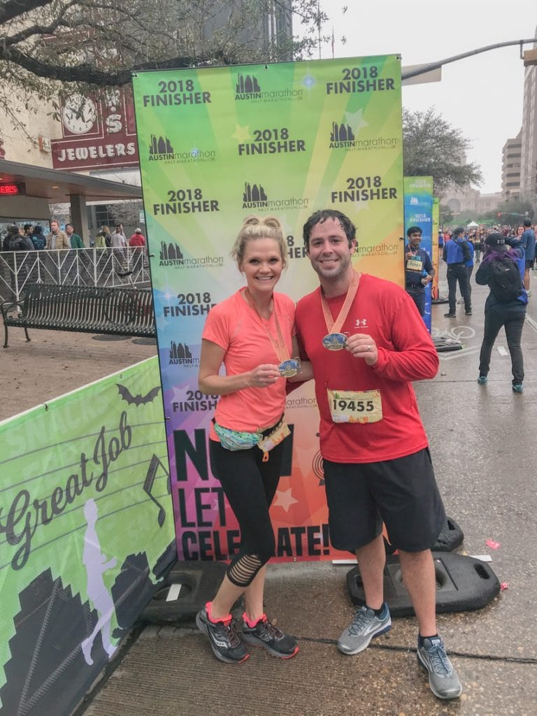 couple holding medals after completing the austin half marathon