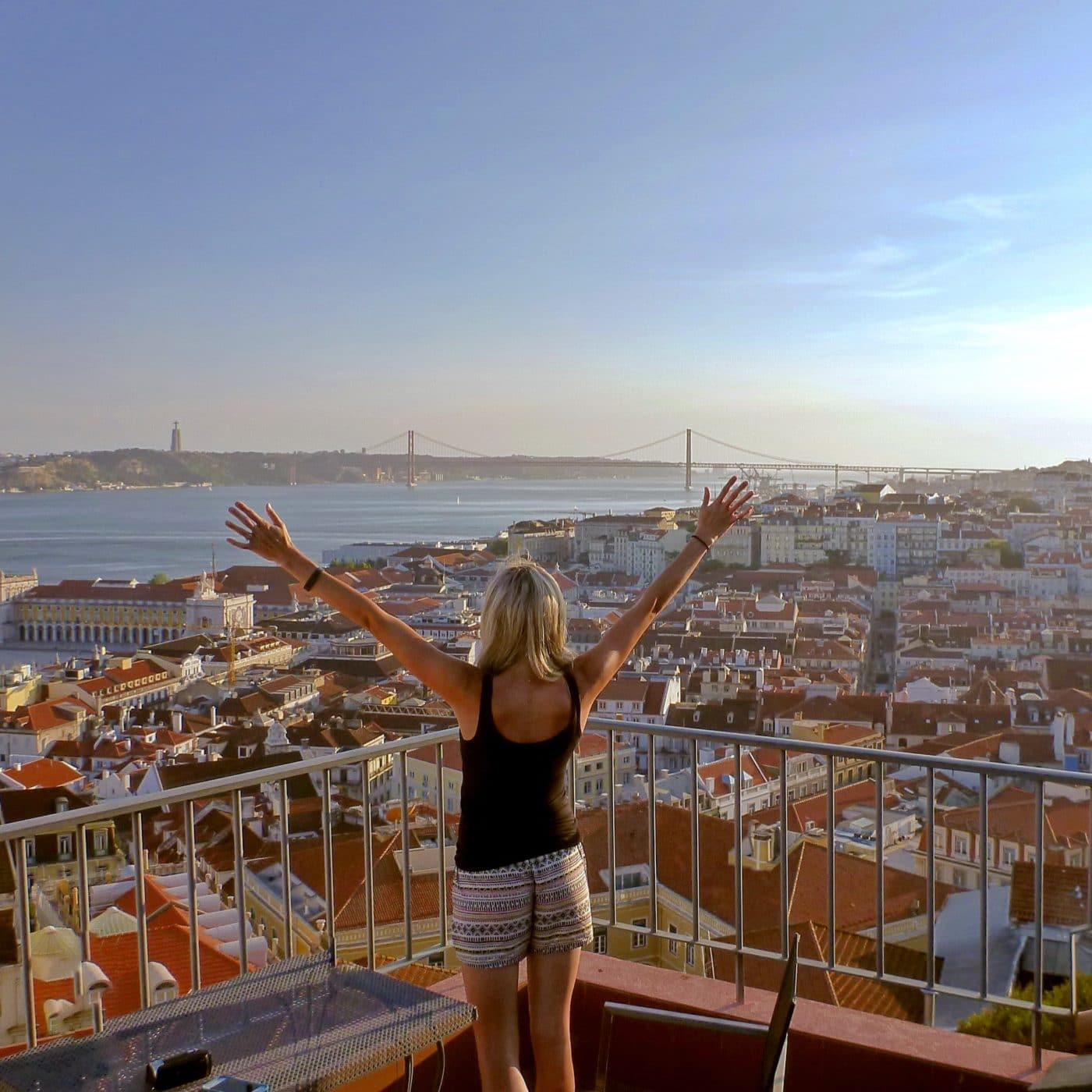 Women on rooftop patio in Lisbon Portugal with arms open wide
