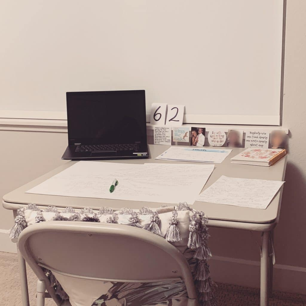 card table set up as writing space with laptop, countdown, and photos