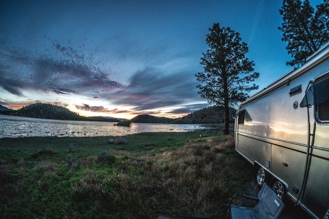 Airstream parked near lake with sunset