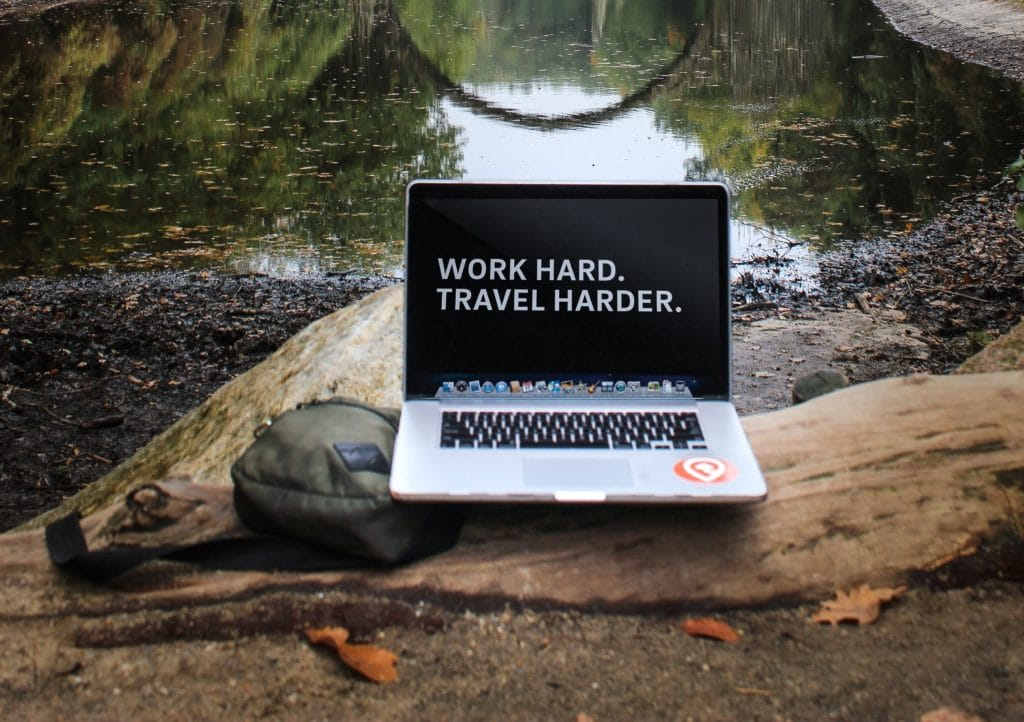 computer outdoors that says work hard travel harder