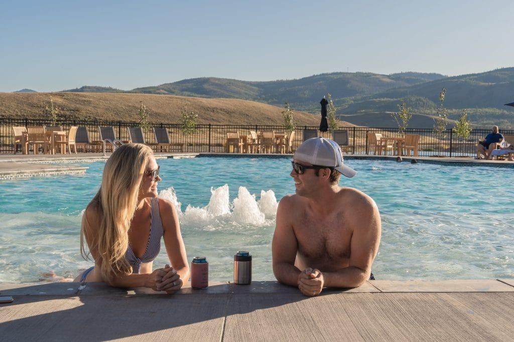 Couple enjoying beers by River Run RV Resort Pool