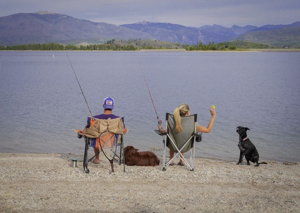 couple and two dogs sitting on shore Fishing at Grand Lake, Colorado