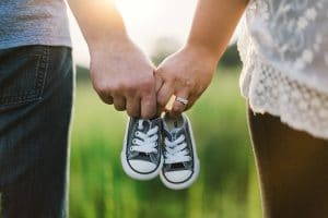 couple holding infant shoes in hands