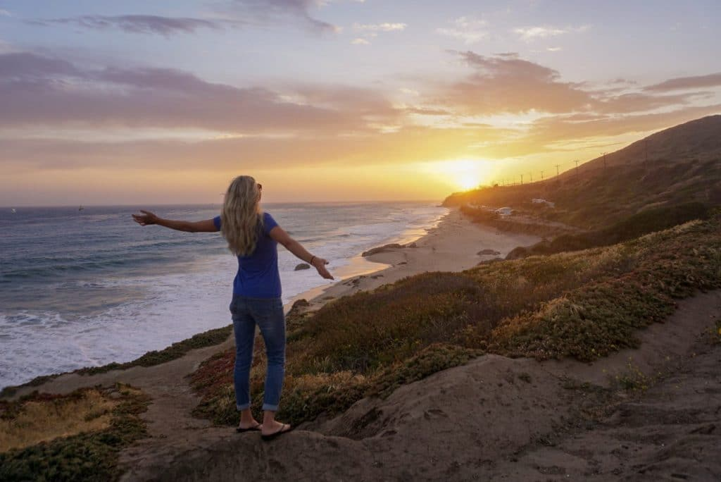 Woman with open arms towards sunset on a California beach