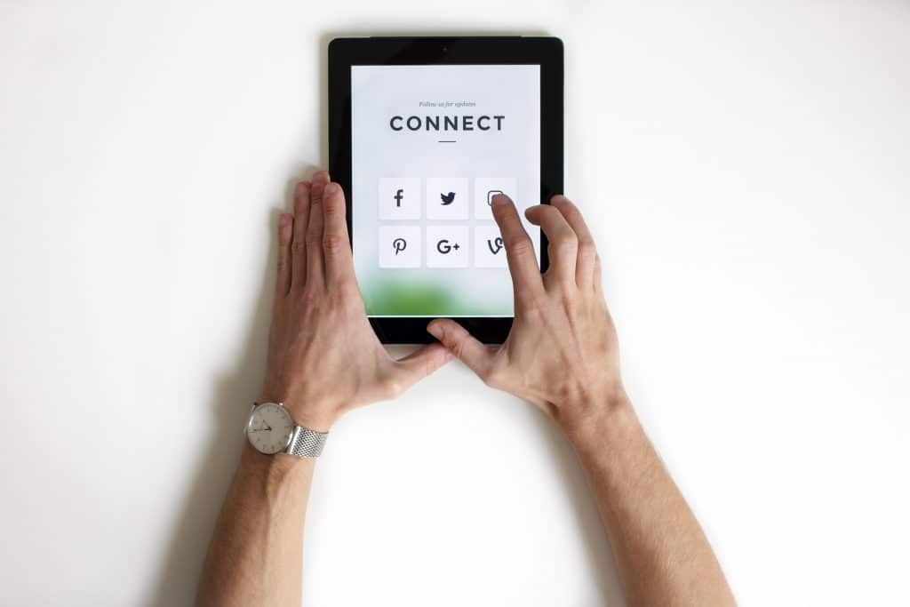 person clicking to connect to social media on ipad