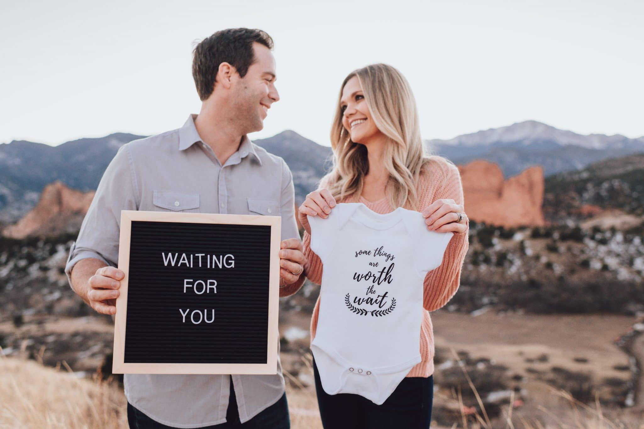 Adopting couple holding sign and onesie waiting for adoption