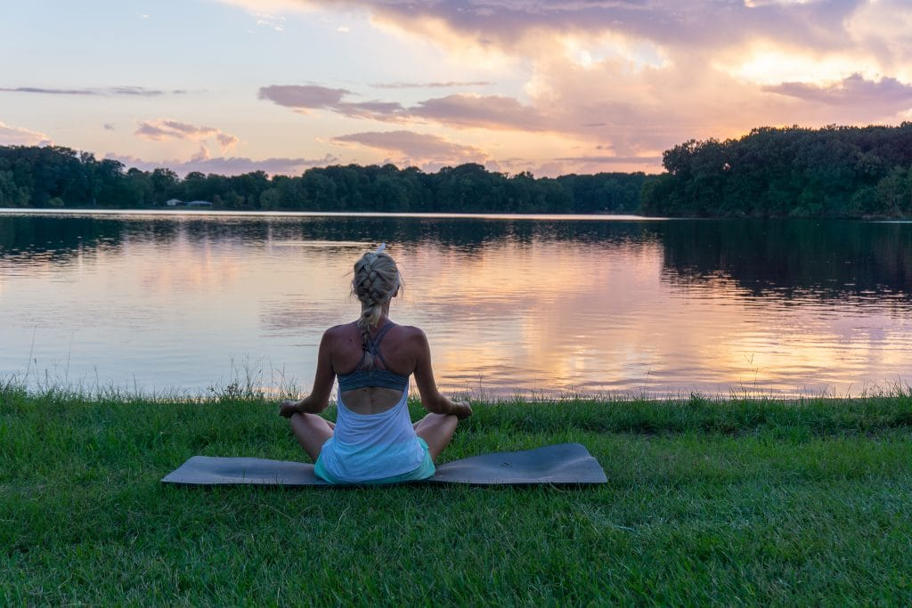 woman doing yoga by a lake at sunset