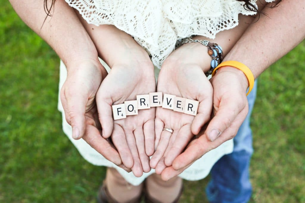 Couples hands together with scrabble tiles spelling out the word forever
