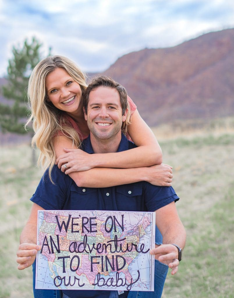 "Couple holding map that says ""we're on an adventure to find our baby"" for domestic infant adoption announcement"