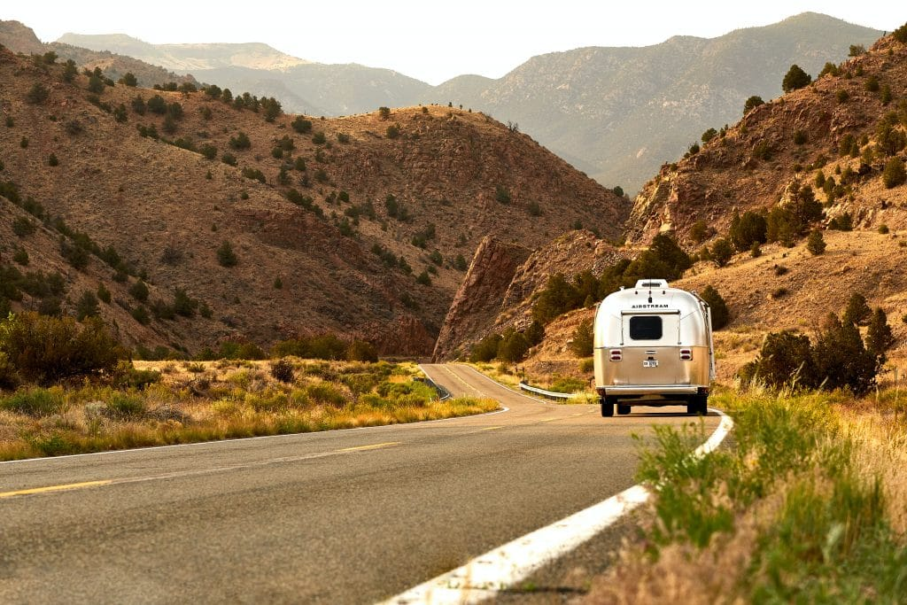Airstream camper being towed on a scenic mountain road