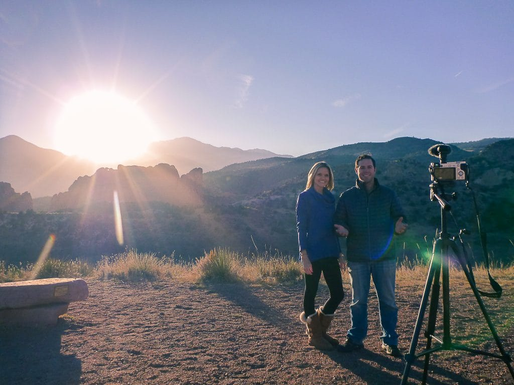 camera on a tripod filming a couple with beautiful mountain scenery behind them